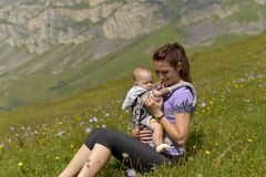 Молодая мать с небольшим ребенком в перемещения рюкзак-нося в горах стоковые фотографии rf