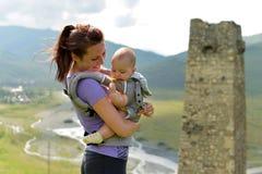 Молодая мать с небольшим ребенком в перемещения рюкзак-нося в горах стоковое фото rf