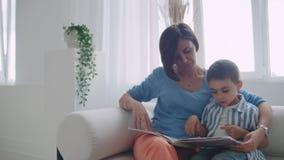 Молодая мать с ребенком читая книгу сидя в ярком белом интерьере дома в живущей комнате на сток-видео