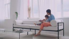 Молодая мать с ребенком читая книгу сидя в ярком белом интерьере дома в живущей комнате на акции видеоматериалы