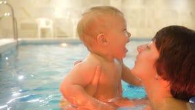 Молодая мать с ребёнком плавает и имеет потеха в бассейне Счастливый мальчик плавает в бассейне вместе с его сток-видео
