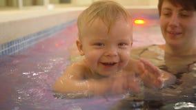 Молодая мать с ребёнком плавает и имеет потеха в бассейне Счастливый мальчик плавает в бассейне вместе с его акции видеоматериалы