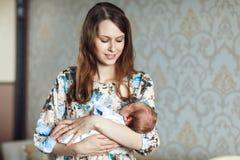 Молодая мать тряся ребенка в ее оружиях Стоковая Фотография RF
