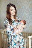 Молодая мать тряся ребенка в ее оружиях Стоковое Фото