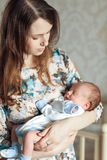 Молодая мать тряся ребенка в ее оружиях Стоковые Изображения