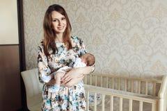 Молодая мать тряся ребенка в ее оружиях Стоковое Изображение RF