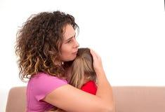 Молодая мать утихомиривает ее дочь Девушка плачет и ее мать обняла ее с любовью стоковая фотография rf