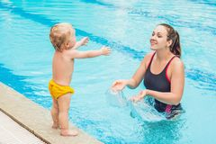 Молодая мать учит ее маленькому сыну, как поплавать в бассейне стоковое изображение rf