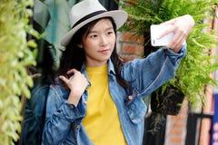 Молодая милая азиатская женщина в непринужденном стиле делая selfie с ее смартфоном в городской предпосылке outdoors города, self стоковое изображение