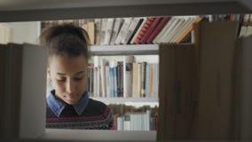 Молодая милая Афро-американская женщина в школьной библиотеке акции видеоматериалы