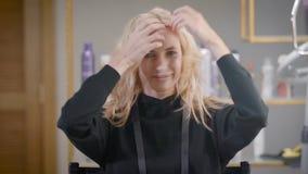 Молодая милая белокурая женщина демонстрирует ее стиль причесок в салоне парикмахерских услуг, развевая голове и замках сток-видео