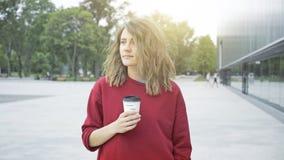 Молодая милая вскользь девушка брюнет выпивает кофе outdoors в утре стоковое изображение