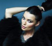 Молодая милая девушка брюнета с представлять макияжа моды элегантный в меховой шыбе с ювелирными изделиями на голубой предпосылке стоковое фото rf