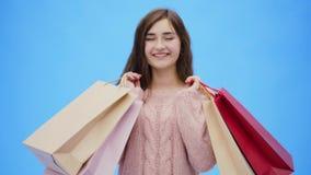 Молодая милая девушка делая неимоверно приятные покупки Во время этого она поднимает ее руки и хозяйственные сумки вверх На этих  видеоматериал