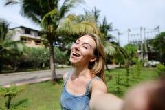 Молодая милая девушка звоня видео- smartphone около пальм в предпосылке стоковое фото rf