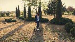 Молодая милая девушка идет с ее йоркширским терьером в парке на заходе солнца сток-видео