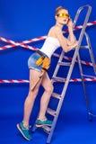 Молодая, милая девушка построителя в белой рубашке, поясе построителя, построителе Стоковые Изображения RF