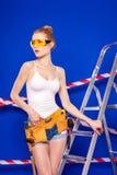 Молодая, милая девушка построителя в белой рубашке, поясе построителя, построителе Стоковая Фотография
