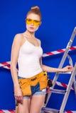 Молодая, милая девушка построителя в белой рубашке, поясе построителя, построителе Стоковые Изображения
