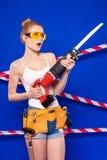 Молодая, милая девушка построителя в белой рубашке, поясе построителя, построителе Стоковые Фотографии RF