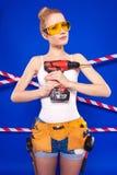 Молодая, милая девушка построителя в белой рубашке, поясе построителя, построителе Стоковое Изображение