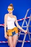 Молодая, милая девушка построителя в белой рубашке, поясе построителя, построителе Стоковое фото RF