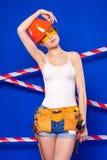 Молодая, милая девушка построителя в белой рубашке, поясе построителя, шлем, Стоковые Фотографии RF