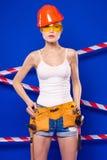 Молодая, милая девушка построителя в белой рубашке, поясе построителя, шлем, Стоковая Фотография RF