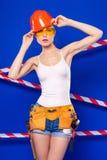 Молодая, милая девушка построителя в белой рубашке, поясе построителя, шлем, Стоковое Изображение