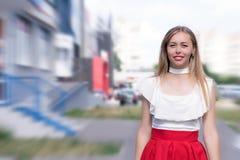 Молодая милая девушка стоя на улице blured предпосылка стоковые фотографии rf