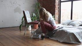 Молодая милая девушка с щеткой и палитра сидя около изображения чертежа мольберта Искусство, творческие способности, хобби, рисуя сток-видео