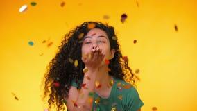 Молодая милая девушка с confetti вьющиеся волосы дуя на желтой предпосылке Женщина празднуя, показывает утеху и счастье сток-видео