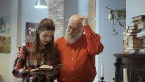 Молодая милая девушка читает интересную книгу вместе с дедом сток-видео