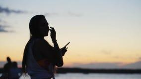 Молодая милая женщина активно танцует в под открытым небом толпить партии пляжа на заходе солнца акции видеоматериалы