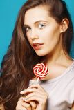 Молодая милая женщина брюнета представляя счастливое жизнерадостное на голубой предпосылке с конфетой, концепции людей образа жиз стоковые изображения rf