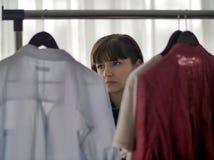 Молодая милая женщина брюнета рассматривая одежды на вешалках стоковое фото