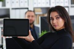 Молодая милая женщина брюнет в таблетке владением офиса в руках Стоковое Фото