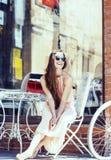 Молодая милая женщина брюнет после ходя по магазинам сидеть на кафе снаружи на усмехаться улицы Стоковые Изображения RF