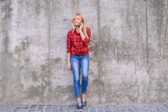 Молодая милая женщина говоря на мобильном телефоне пока имеющ прогулку в черни телефона smartphone телефона мобильного телефона г стоковые изображения rf