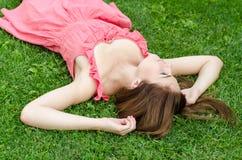 Молодая милая женщина лежа на зеленой траве в парке Стоковое фото RF