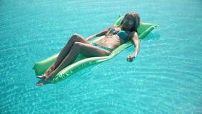 Молодая милая женщина лежа на тюфяке воздуха в бассейне стоковые изображения