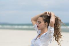 Молодая милая женщина на пляже исправляя ее ponytail Стоковое Изображение
