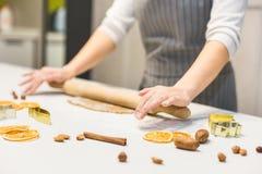 Молодая милая женщина подготавливает тесто и печет пряник и печенья в кухне Веселое рождество и счастливое новое стоковая фотография