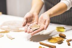 Молодая милая женщина подготавливает тесто и печет пряник и печенья в кухне Она держит отрезок звезды от стоковая фотография rf