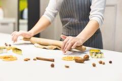 Молодая милая женщина подготавливает тесто и печет пряник и печенья в кухне E стоковые изображения