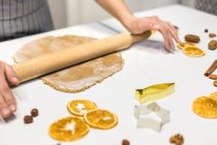 Молодая милая женщина подготавливает тесто и печет пряник и печенья в кухне E стоковое фото
