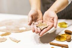 Молодая милая женщина подготавливает тесто и печет пряник и печенья в кухне Она держит отрезок звезды от стоковые изображения