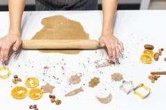 Молодая милая женщина подготавливает тесто и печет пряник и печенья в кухне E стоковое изображение rf