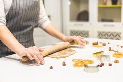 Молодая милая женщина подготавливает тесто и печет пряник и печенья в кухне E стоковая фотография