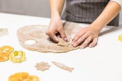 Молодая милая женщина подготавливает тесто и печет пряник и печенья в кухне Она делает форму звезды на стоковая фотография rf